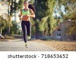 a brunette runner woman runs in ... | Shutterstock . vector #718653652