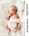 sleeping newborn baby in a wrap ... | Shutterstock . vector #718675372