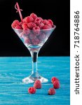 Small photo of A beautiful cocktail glass with ripe raspberries. Making a cocktail, juice, alcoholic beverage.A beautiful cocktail glass with ripe raspberries. Making a cocktail, juice, alcoholic beverage.
