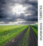 rural road in green field under cloudy sky - stock photo