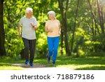senior couple running in park  | Shutterstock . vector #718879186