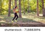 a woman runs through the forest ... | Shutterstock . vector #718883896