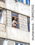 a woman washes a window in a... | Shutterstock . vector #718902502