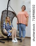Small photo of thin slender girl with a lush girlfriend posing on the camera next to the wicker chair rocking chair. two girls with different proportions of bodies. a slim figure and a fat figure