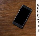 smart phone on brown wooden desk | Shutterstock . vector #719056588