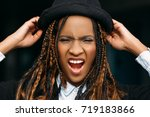 Small photo of Aggressive African American woman. Rage emotion. Modern stylish youth, angry screaming black female, aggression concept
