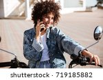 pleased curly girl sitting on... | Shutterstock . vector #719185882