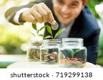 businessman putting coin into... | Shutterstock . vector #719299138