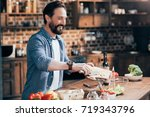 smiling bearded man cooking... | Shutterstock . vector #719343796