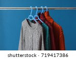 warm woolen sweaters hanging on ... | Shutterstock . vector #719417386
