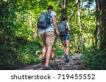 Stock photo couple with a small yellow dog hiking in forest 719455552