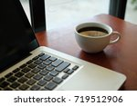 a cup of coffee and latop at... | Shutterstock . vector #719512906