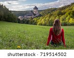 Young woman sitting on grass at Karlstejn castle in Czech Republic.