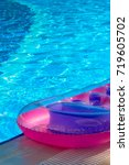 Small photo of colorful air mattress by the swimming pool. summer. vacation.