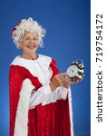 Small photo of Mrs Claus shows Santa that it is almost time to leave