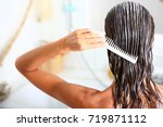 Small photo of woman applying hair care with a comb
