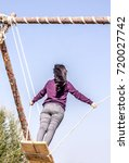 Small photo of Young girl with long hair swings on a swing