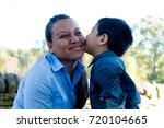 latino son giving a kiss to his ... | Shutterstock . vector #720104665
