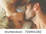 young couple kissing in bed... | Shutterstock . vector #720401182