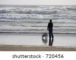 Stock photo a woman walks along the shorline with her dog 720456