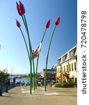 Small photo of Victoria, British Columbia, Canada 2012. View of a nice street art representing a canoa supported by huge disproportionate flowers in the waterfront of the city