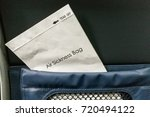 Small photo of Air sickness bag tucked behind airplane seat pocket for nauseous passenger