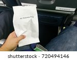 Small photo of Airsick nauseous person holding the air sickness vomit bag prepared to vomit