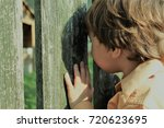 child peaking through fence... | Shutterstock . vector #720623695