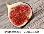 half of fig on wooden table | Shutterstock . vector #720633235