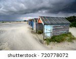 beach huts under a dramatic...