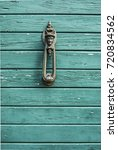 Small photo of old, antique wooden door with nostalgic door knocker with rogue motive