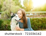 girl playing with a dog outdoors | Shutterstock . vector #721036162