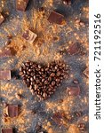 Small photo of Roasted coffee beans in the shape of a heart on the dark stone background with dissipate cocoa, pieces of chocolate and beans. Selective focus. Coffee love concept. Vertical photo.