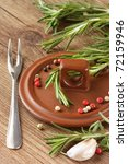 Spices on a ceramic cover, a steel fork and fresh rosemary. - stock photo