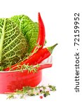 Savoy cabbage and chili in a red ceramic saucepan. - stock photo