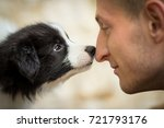 Stock photo happy young man looking at amazing cute border collie puppy sniffing his nose 721793176