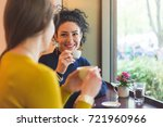 Two Women In A Cafe Smiling An...