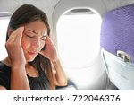 Small photo of Travel plane sick woman. Fear of flying girl in airplane airsick with stress headache and motion sickness or airsickness. Person in airplane with aerophobia scared of flight frustrated sitting.
