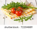 Tomatoes, arugula, garlic on a yellow napkin. - stock photo