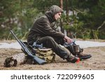 male hunter preparing food with a portable gas burner in a winter forest. Bushcraft, hunting and people concept - stock photo