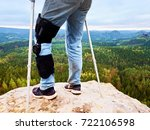 Small photo of Close Up Of Man Walking With Crutches in nature. Man legs in jeans with adjustable Bandage on pain knee.