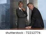 Senior business man and woman in a boardroom smiling looking at camera - stock photo