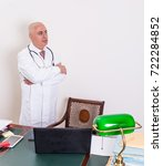 Small photo of Aback doctor in his studio. Use new technologies. The office has an antique desk and a green lamp shade of green.