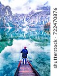 Small photo of Young man backpacker dressed red hat and blue jacket admiring pristine untouched nature rear view over green water of Lake Braies - lago di Braies and Dolomite alpine mountains in background. Italy.