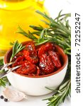 Dried tomatoes, garlic, rosemary and olive oil. - stock photo