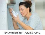 woman tightening pipe under... | Shutterstock . vector #722687242