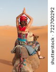 Small photo of Girl wearing sandals, harem pants and a red turban rides a camel across the thin sand dunes of the in Western Sahara Desert, Morocco, Africa, holding her hands above her head in a praying position.