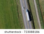 Aerial view over a transport truck and a small car passing each other along a small country side road in rural Quebec, Canada.