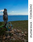 Small photo of An ancient idol, carved from a tree, stands on the shore of a lake. Bright blue water, clear sky, green grass. Skyline. At the feet of the figure are colored ribbons. Subject of worship.