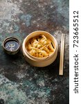Small photo of Steamed dumplings Gyoza in bamboo steamer with chopsticks and sauce on metal background copy space